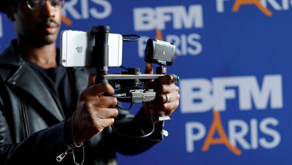 Un journaliste devant un logo de BFM  - Sputnik France