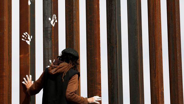An activist paints the U.S.-Mexico border wall between Ciudad Juarez and New Mexico as a symbol of protest against U.S. President Donald Trump's new immigration reform in Ciudad Juarez, Mexico February 26, 2017. - Sputnik France