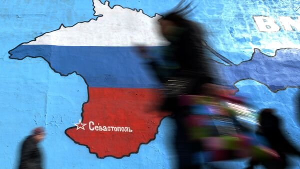 Pedestrians walk past an wall painting depicting a map of Crimean peninsula bearing the colours of Russia's national flag in Moscow, on March 31, 2014. - Sputnik France