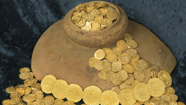 Over 350 gold coins from a sunken Spanish Treasure are seen in an undated handout picture courtesy of 1715 Fleet - Queens Jewels. Florida treasure hunters found the trove of $4.5 million worth of Spanish gold coins 300 years to the day after a fleet of ships sunk in a hurricane while en route from Havana to Spain, the salvage owner said August 19, 2015 - Sputnik France