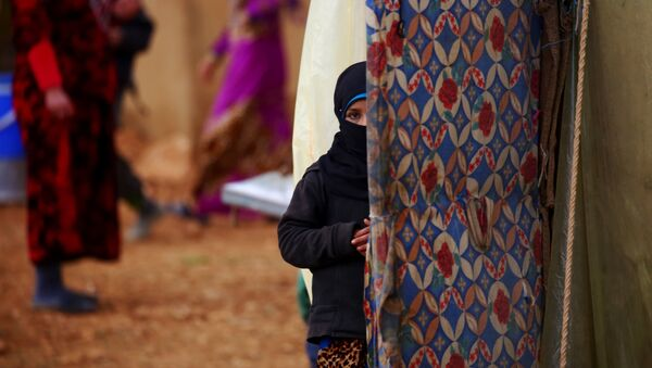 A displaced Syrian woman, who fled her hometown due to clashes between regime forces and the Islamic State (IS) group, stands outside a tent in Kharufiyah, 18 kilometres south of Manbij, on March 4, 2017. - Sputnik France
