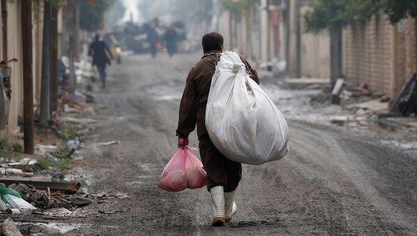 Un homme irakien porte des marchandises de l'aide humanitaire dans le district d'Al Ghizlane alors que la lutte contre les terroristes de l'État islamique se poursuit à Mosul, en Irak - Sputnik France