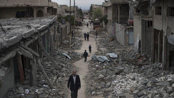 Des irakiens passent devant des ruines dans la ville de Mossoul - Sputnik France