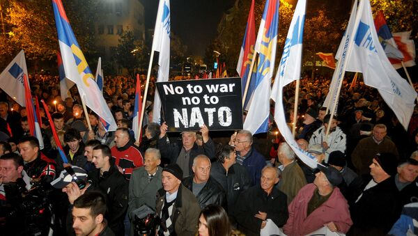 An opposition supporter holds a banner that reads No to war - no to NATO during protest in downtown Podgorica, Montenegro, Saturday, Dec. 12, 2015 - Sputnik France