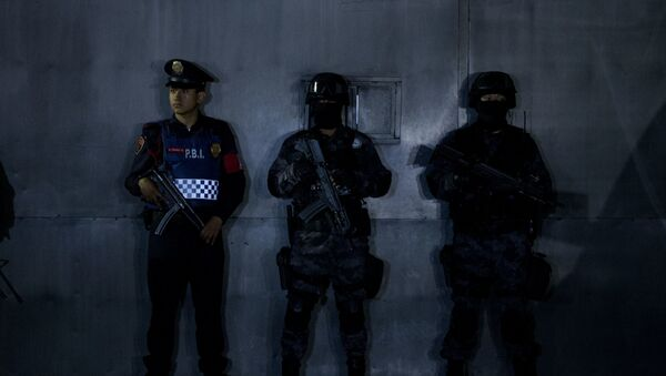 Police stand guard outside the entrance gate to the airport hangar of Mexico's Attorney General office, in Mexico City, during the arrival of drug lord Hector El Guero Palma, Wednesday, June 15, 2016 - Sputnik France