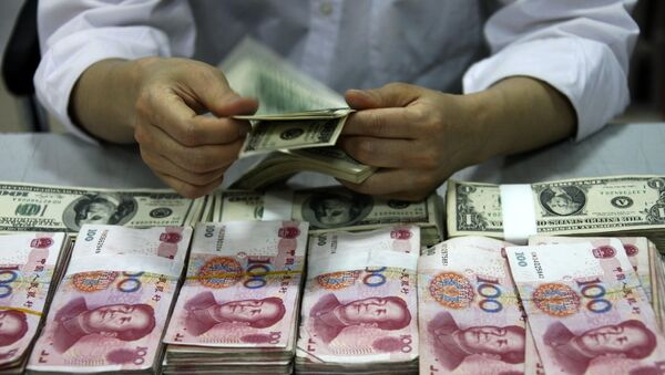 This picture taken on September 24, 2013 shows US dollar notes being counted next to stacks of Chinese 100 yuan (RMB) bank notes at a bank in Huaibei, in eastern China's Anhui province. With deals from London to Singapore, China is seeking to have its yuan currency used more widely around the world and challenge the hegemony of the almighty dollar. - Sputnik France