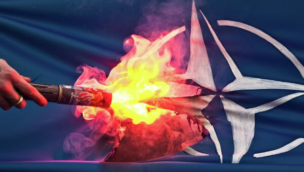 A member of the banned National-Bolshevik Party sets on fire a flag bearing the North Atlantic Treaty Organization (NATO) logo during a protest on April 5, 2010 - Sputnik France