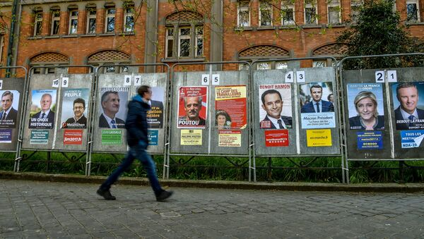 A man walks past campaign posters of the eleven candidates running for the French presidential election in Lille on April 10, 2017. - Sputnik France