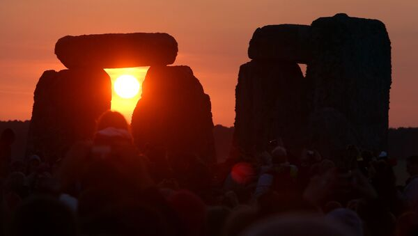 The rising sun is seen through the standing stones at the prehistoric monument Stonehenge, near Amesbury in Southern England, on June 21, 2014, as revelers gather to celebrate the 2014 summer solstice, marking the longest day of the year. - Sputnik France