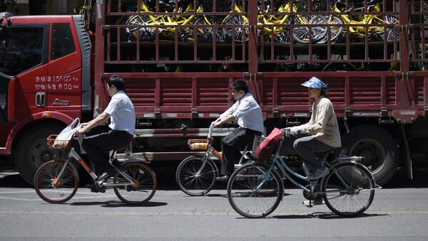A group of people ride past a truck full of share bicycles in Beijing on May 24, 2017. - Sputnik France