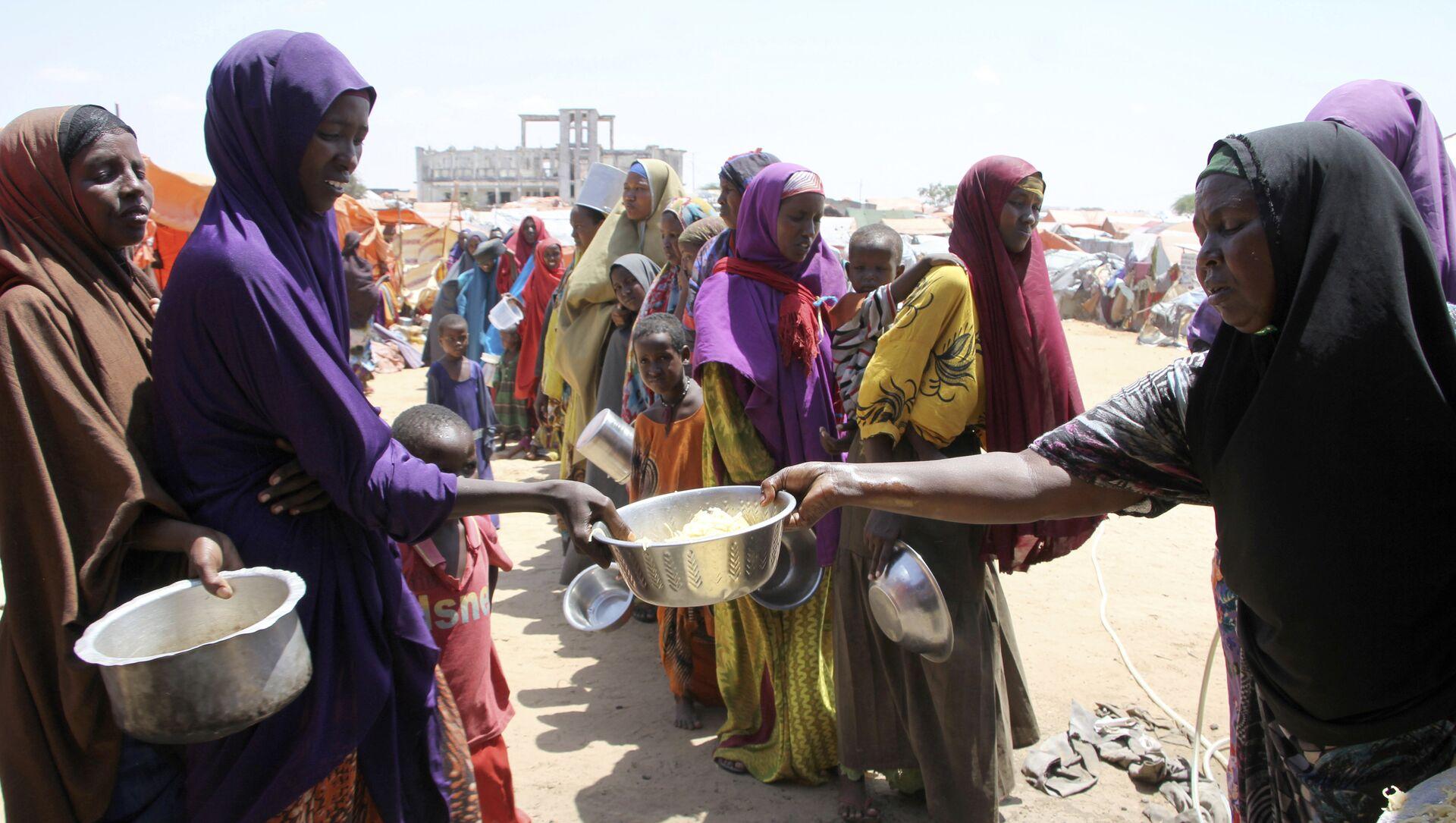 Des femmes reçoivent de la nourriture à Mogadiscio, en Somalie - Sputnik France, 1920, 18.08.2021