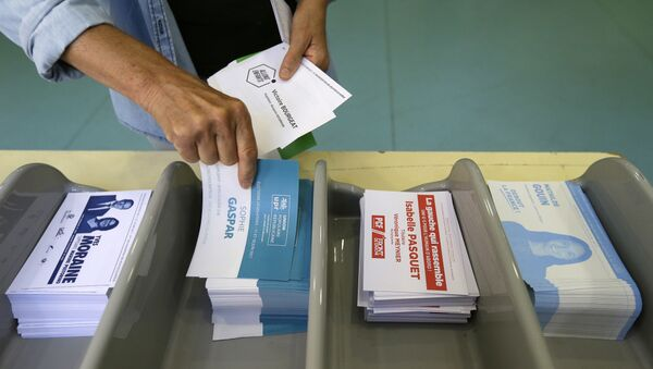 Voter picks up ballots at a polling station before voting for the first round of parliamentary elections in Marseille, southern France, Sunday, June 11, 2017 - Sputnik France