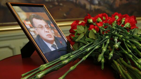 Flowers lay next to a portrait in memory of Russian Ambassador to Turkey Andrei Karlov, who was fatally shot by a Turkish policeman Monday in a gathering in Ankara, Turkey, before their talks on Syria in Moscow, Russia, Tuesday, Dec. 20, 2016. - Sputnik France