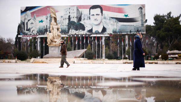People walk past a billboard depicting Syria's President Bashar al-Assad at Saadallah al-Jabri Square, in the government controlled area of Aleppo, Syria December 17, 2016 - Sputnik France