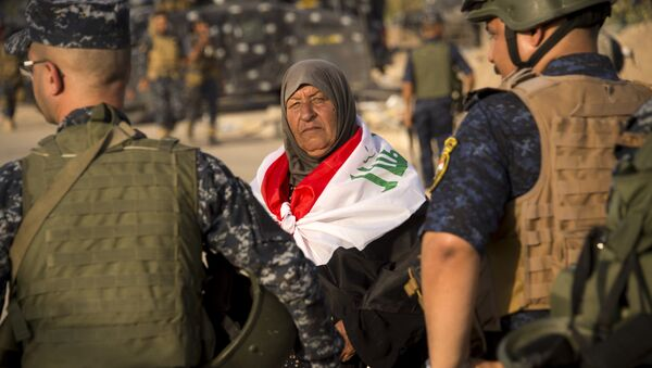An elderly woman draped in Iraq's na tional flag looks on as she stands by Iraq's federal police members celebrating in the Old City of Mosul on July 9, 2017 after the government's announcement of the liberation of the embattled city. - Sputnik France