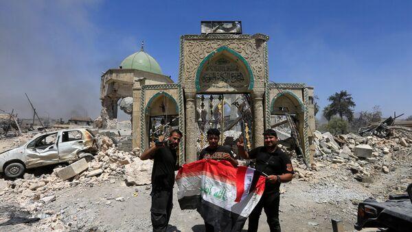 Les membres du Service antiterroriste posent pour une photo avec un drapeau irakien devant les ruines de la mosquée Grand al-Nuri dans la vieille ville de Mossoul, en Irak, le 30 juin 2017 - Sputnik France