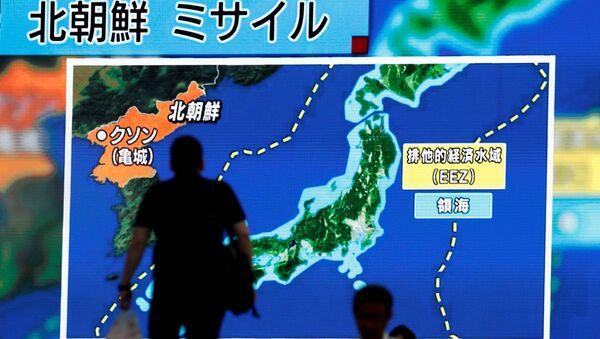 Men walk past a street monitor showing news of North Korea's intercontinental ballistic missile test in Tokyo, Japan. (File) - Sputnik France