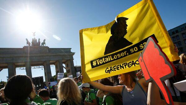 Les gens tiennent des bannières alors qu'ils protestent près de la Porte de Brandebourg, à côté de l'ambassade des États-Unis, contre le retrait des États-Unis de l'accord de Paris sur le changement climatique, à Berlin, en Allemagne, le 2 juin 2017 - Sputnik France
