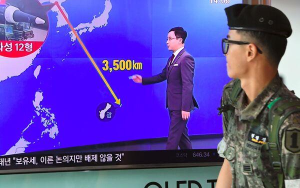 Un soldat sud-coréen passe devant un écran de télé avec une infographie montrant la distance entre la Corée du Nord et Guam, dans une gare à Séoul, le 9 août 2017 - Sputnik France