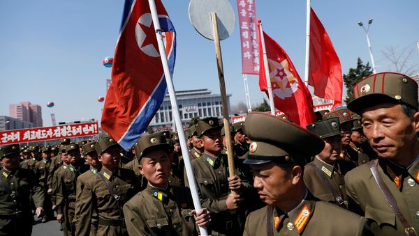 North Korean soldiers carry flags as they visit the newly constructed residential complex after its opening ceremony in Ryomyong street in Pyongyang, North Korea April 13, 2017 - Sputnik France