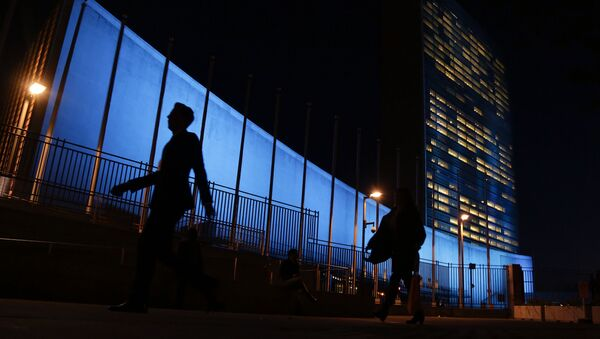 Pedestrians walk by United Nations Headquarters, lit up in blue light, a day in advance of the 70th Anniversary of the U.N., Friday, Oct. 23, 2015, in New York - Sputnik France