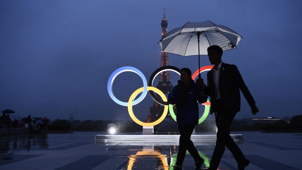 People carrying an umbrella walk past the Olympics Rings on the Trocadero Esplanade near the Eiffel Tower in Paris, on September 13, 2017, after the International Olympic Committee named Paris host city of the 2024 Summer Olympic Games. - Sputnik France