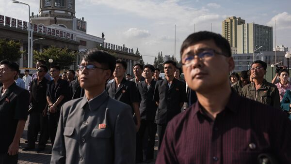 Spectators listen to a television news brodcast of a statement by North Korean leader Kim Jong-Un, before a public television screen outside the central railway station in Pyongyang on September 22, 2017 - Sputnik France
