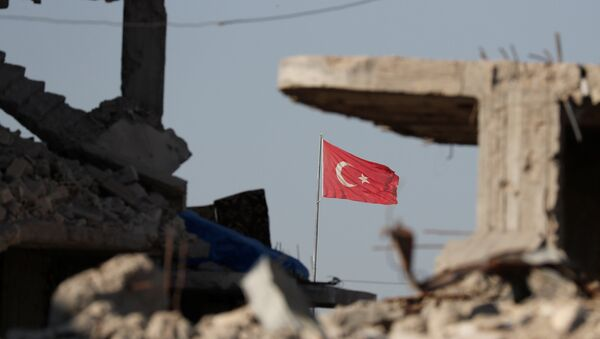 Turkish flag flutters at Turkey's border gate, as pictured on Syria side, overlooking the ruins of buildings destroyed during fightings with the Islamic State militants in Kobani, Syria October 11, 2017. - Sputnik France