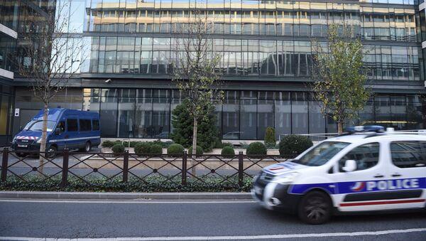 The headquarters of France's Anti-Terrorism Sub-Directorate (Sous Direction de la Lutte Anti-Terroriste, SDAT) is reflected onto a glass building as a police car drives past on November 15, 2015 - Sputnik France