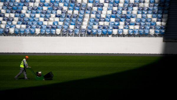 Рабочий стрижет газон на строящемся стадионе Нижний Новгород. - Sputnik France
