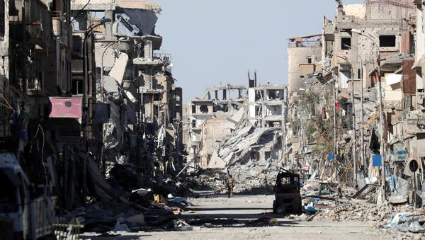 A fighter of Syrian Democratic Forces stands amidst the ruins of buildings near the Clock Square in Raqqa, Syria October 18, 2017 - Sputnik France