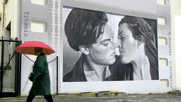 A woman walks in front a wall in Cannes, southern France, representing greetings from the cinema with Leonardo Di Caprio with Kate Winslet in Titanic , Friday Jan. 23, 2009. - Sputnik France