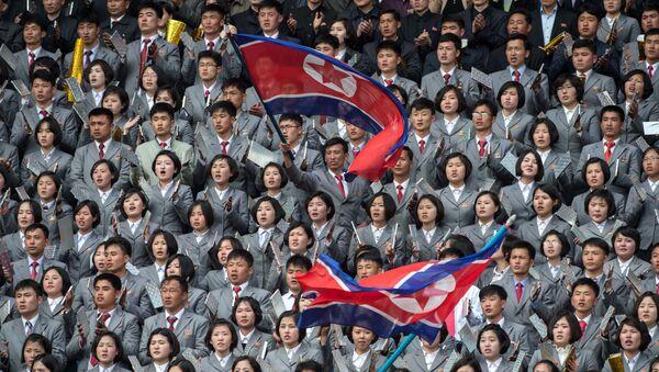 Северокорейцы размахивают флагом в поддержку своей команды во время соревнований по футболу - Sputnik France
