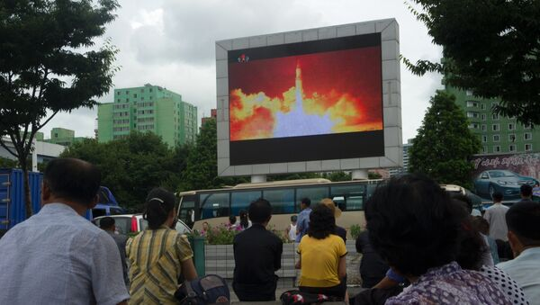 People watch as coverage of an ICBM missile test is displayed on a screen in a public square in Pyongyang on July 29, 2017. - Sputnik France