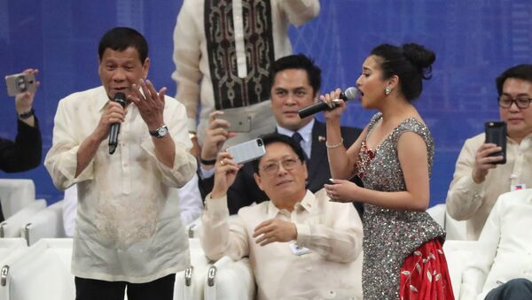Rodrigo Duterte (L), President of the Philippines, sings a duet with a female singer during a gathering at Lusail Sports Arena in Lusail, 20km north of the Qatari capital on April 15, 2017. - Sputnik France