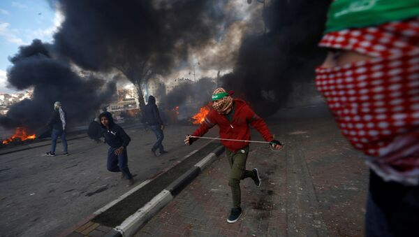 Palestinian protesters run during clashes with Israeli troops at a protest against U.S. President Donald Trump's decision to recognize Jerusalem as the capital of Israel, near the Jewish settlement of Beit El, near the West Bank city of Ramallah December 7, 2017. - Sputnik France