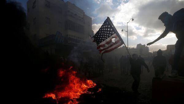 Палестинцы жгут американский флаг во время столкновений с израильской полицией в связи с протестами против решения Дональда Трампа признать Иерусалим столицей Израиля - Sputnik France