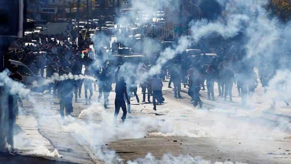 Palestinian demonstrators react to tear gas fired by Israeli troops during clashes at a protest against U.S. President Donald Trump's decision to recognize Jerusalem as the capital of Israel, in the West Bank city of Bethlehem December 9, 2017 - Sputnik France