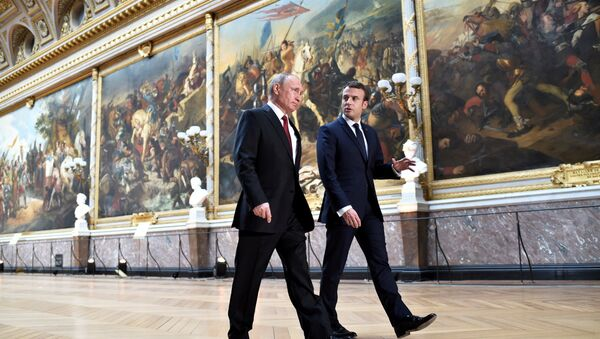 French President Emmanuel Macron (R) speaks to Russian President Vladimir Putin (L) in the Galerie des Batailles (Gallery of Battles) as they arrive for a joint press conference at the Chateau de Versailles before the opening of an exhibition marking 300 years of diplomatic ties between the two countries in Versailles, France, May 29, 2017 - Sputnik France