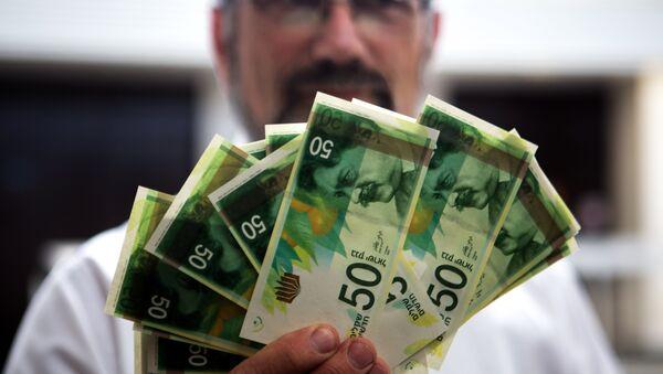An employee of Bank of Israel holds new 50 Shekels' bills during a press conference at the bank's headquarters in Jerusalem on September 10 2014 - Sputnik France