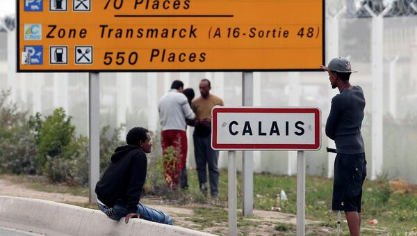 Migrants stand near a city sign along a road near the makeshift camp called The New Jungle in Calais, France, August 19, 2015 - Sputnik France