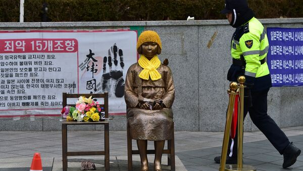 A South Korean policeman walks past a statue (C) of a teenage girl in traditional costume called the peace monument for former comfort women who served as sex slaves for Japanese soldiers during World War II, in front of the Japanese embassy in Seoul on December 29, 2015. - Sputnik France