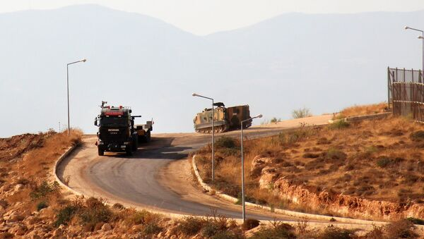 A picture taken on October 11, 2017, from the Syrian village of Atme in the northwestern province of Idlib shows Turkish military vehicles driving around a military base on the Turkish side of the border with Syria. - Sputnik France