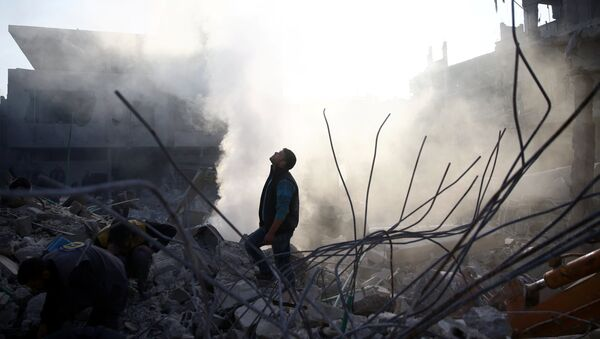 A man stands on rubble of damaged buildings after an airstrike in the besieged town of Hamoria, Eastern Ghouta, in Damascus, Syria - Sputnik France
