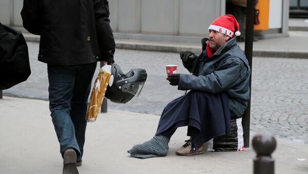 A homeless person wearing a Santa Claus hat begs for money on December 21, 2012 in Paris, a few days before Christmas. - Sputnik France