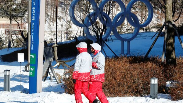 Volunteers walk beside the Olympic rings at the Alpensia resort for the upcoming 2018 Pyeongchang Winter Olympic Games in Pyeongchang, South Korea, January 23, 2018 - Sputnik France