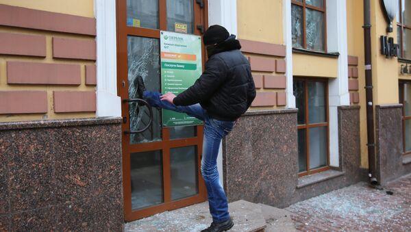 Un extrémiste ukrainien essait de briser une porte d'une succursale de la banque russe Sberbank à Kiev - Sputnik France