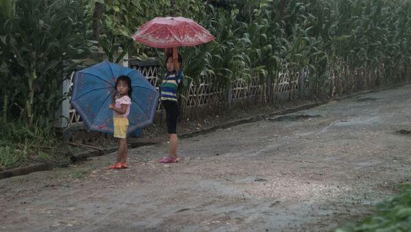 Дети укрываются от дождя под зонтами на юге Пхеньяна - Sputnik France