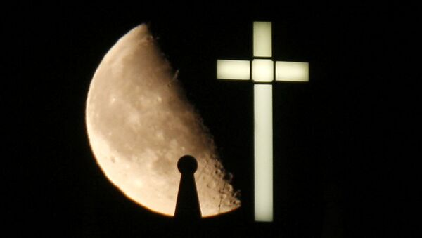 A third quarter Buck Moon rises behind a spire on the top of the bell tower next to a lighted cross - Sputnik France