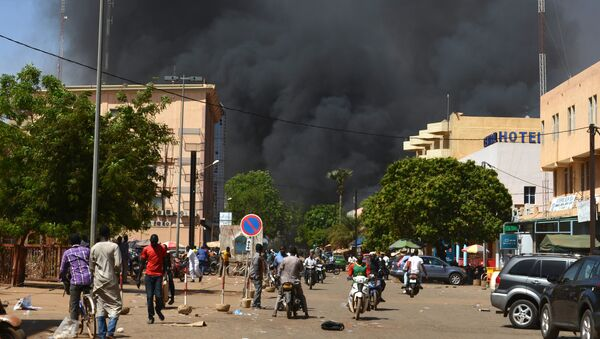 People watch as black smoke rises as the capital of Burkina Faso came under multiple attacks on March 2, 2018, targeting the French embassy, the French cultural centre and the country's military headquarters - Sputnik France